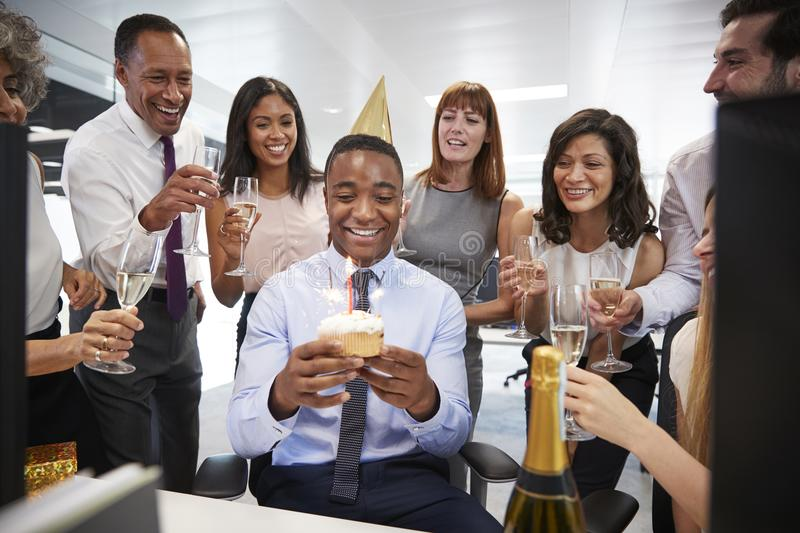 Colleagues gathered at a man�s desk to celebrate a birthday stock image