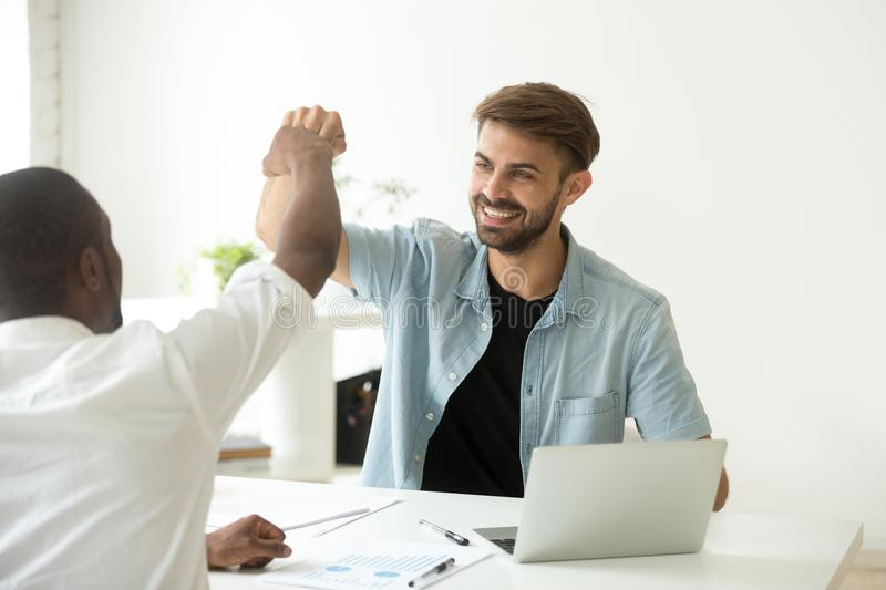 Colleagues giving fist bumps after reaching shared business goal stock photography