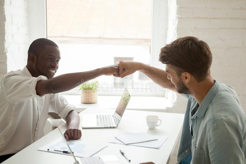 Colleagues giving fist bumps after reaching shared goal. Two workers giving fist bump, celebrating business achievement with arms up, congratulating with royalty free stock image