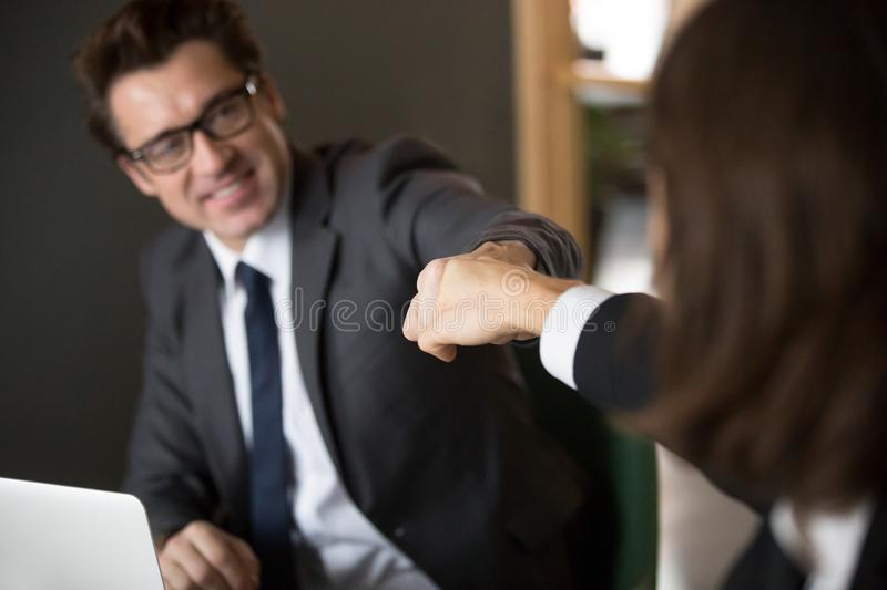 Colleagues giving fists bump celebrating shared business achieve. Close up of middle aged business colleagues giving fists bumps celebrating shared goal royalty free stock photo