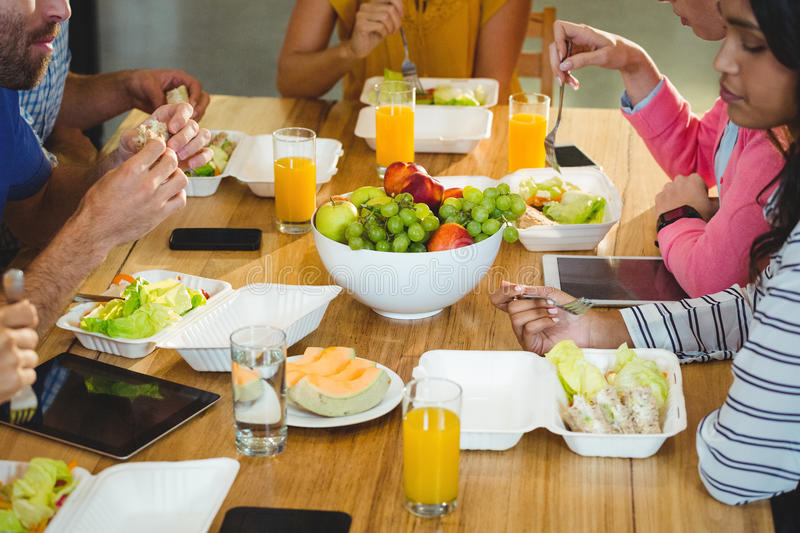 Colleagues having breakfast in office royalty free stock photography