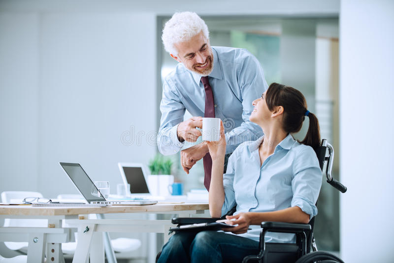 Colleagues having a coffee break. Businessman giving a cup of coffee to her disabled female colleague during a break at office, assistance and friendship concept stock photo