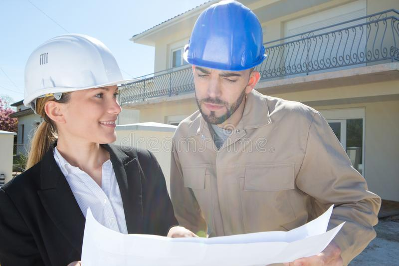 Colleagues with house plans outdoors royalty free stock images