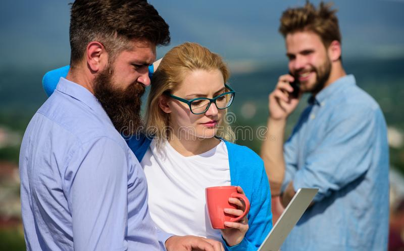 Colleagues with laptop work outdoor sunny day, nature background. Business partners meeting non formal atmosphere. Colleagues looking at screen laptop while stock images