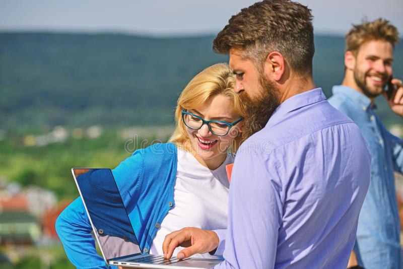 Colleagues with laptop work outdoor sunny day, nature background. Business partners meeting non formal atmosphere. Colleagues looking at screen laptop while royalty free stock images