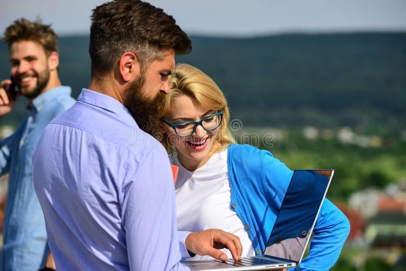Colleagues with laptop work outdoor sunny day, nature background. Business partners meeting non formal atmosphere. Colleagues looking at screen laptop while royalty free stock photo