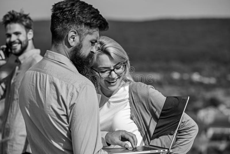 Colleagues with laptop work outdoor sunny day, nature background. Business partners meeting non formal atmosphere. Colleagues looking at screen laptop while royalty free stock photography