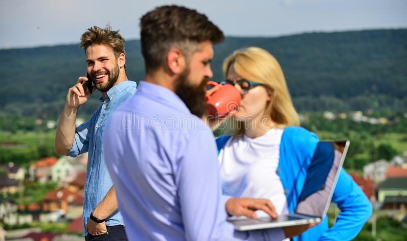 Colleagues with laptop work outdoor sunny day, nature background. Colleagues looking at screen laptop while man talking. Colleagues with laptop work outdoor royalty free stock images