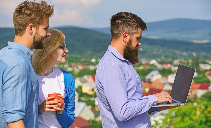 Colleagues with laptop work outdoor sunny day, nature skyline background. Business partners meeting non formal. Atmosphere. Coffee break concept. Colleagues stock photo