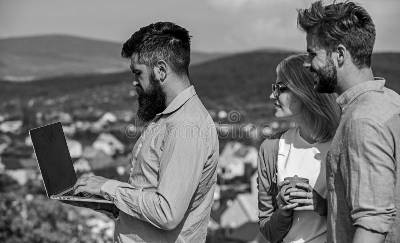 Colleagues with laptop work outdoor sunny day, nature skyline background. Business partners meeting non formal. Atmosphere. Coffee break concept. Colleagues royalty free stock photo