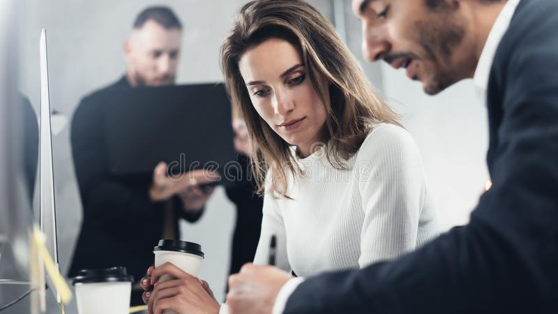 Colleagues are looking for a business solution during work process at sunny office.Business people meeting concept. Blurred background.Horizontal.Cropped royalty free stock image