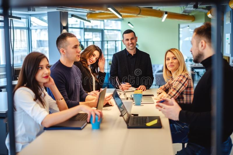 Colleagues looking at one man at the office meeting stock images