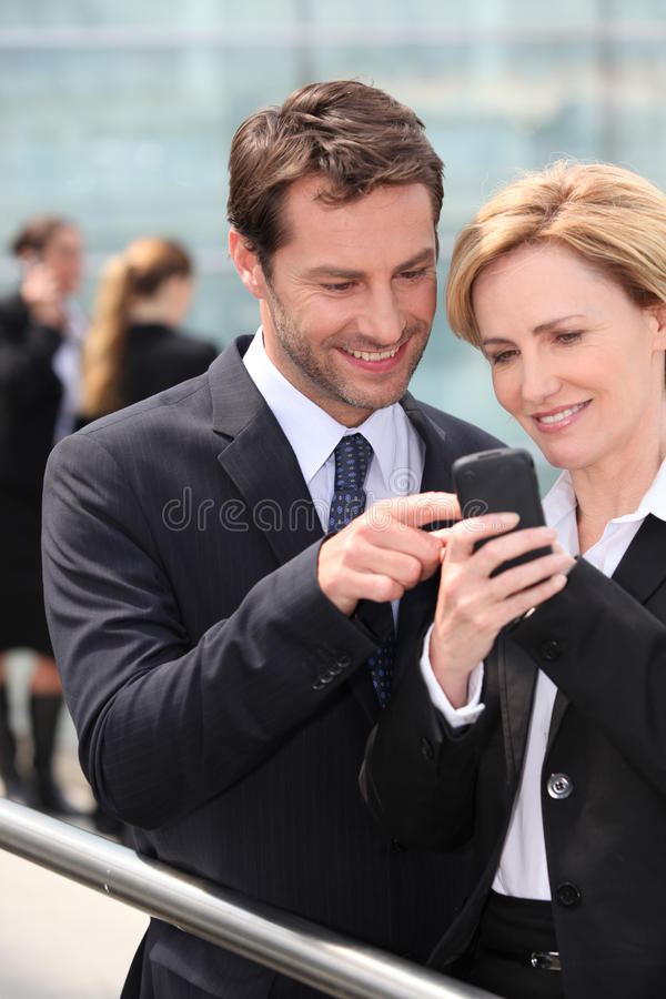 Colleagues looking at phone stock photo