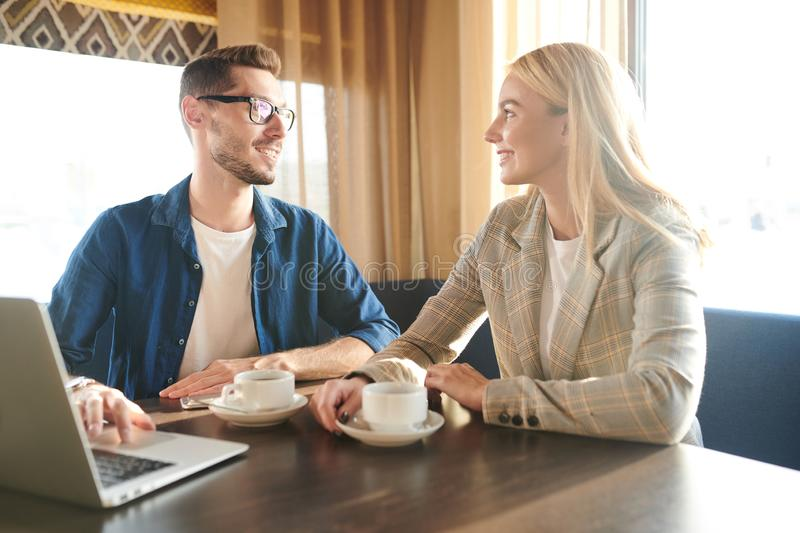 Colleagues at meeting in cafe. Happy young elegant blonde businesswoman and her colleague in casualwear discussing working moments by cup of tea in cafe stock photography