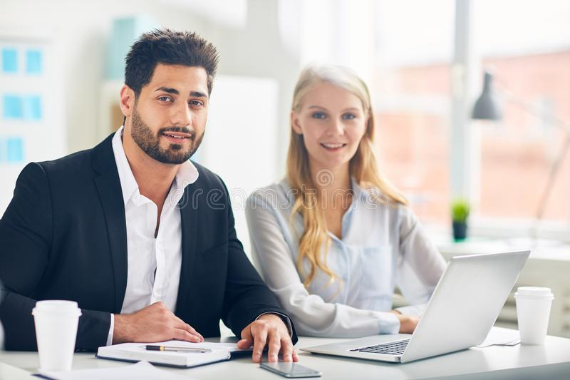 Colleagues in office. Two successful colleagues in formalwear looking at camera by their workplace in office royalty free stock photos