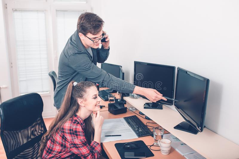 Colleagues in office working on desktop computer stock photo