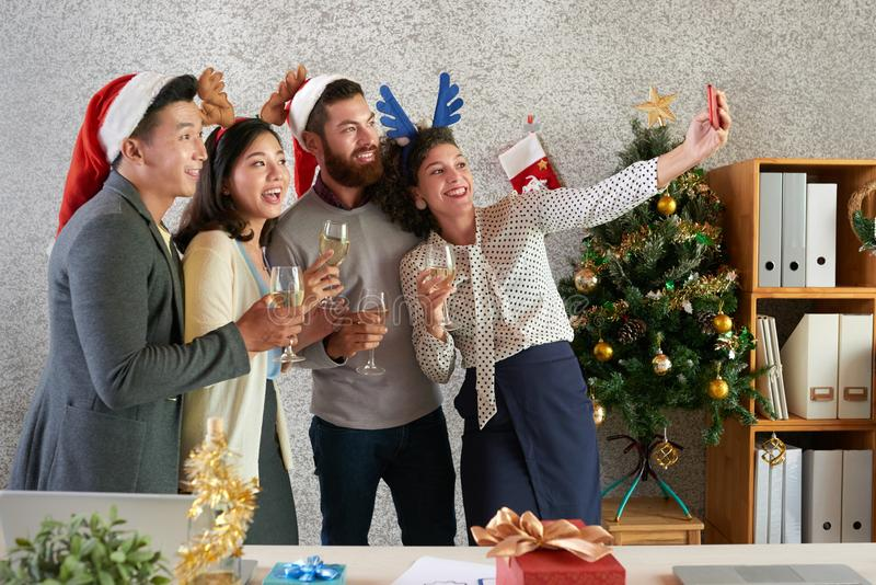 Colleagues photographing at Christmas party stock images