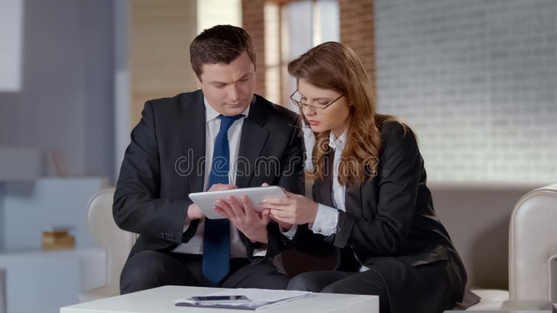 Colleagues planning startup on tablet together, discussing business issues stock image