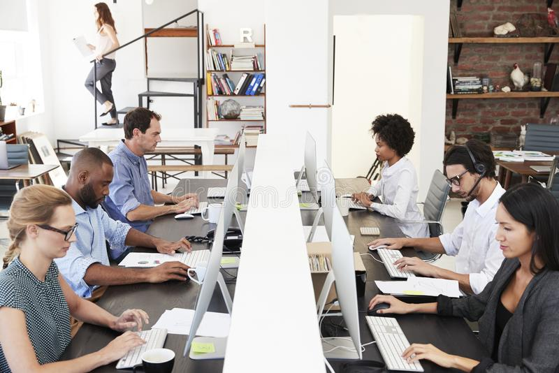 Colleagues sit using computers in a busy open plan office royalty free stock photo