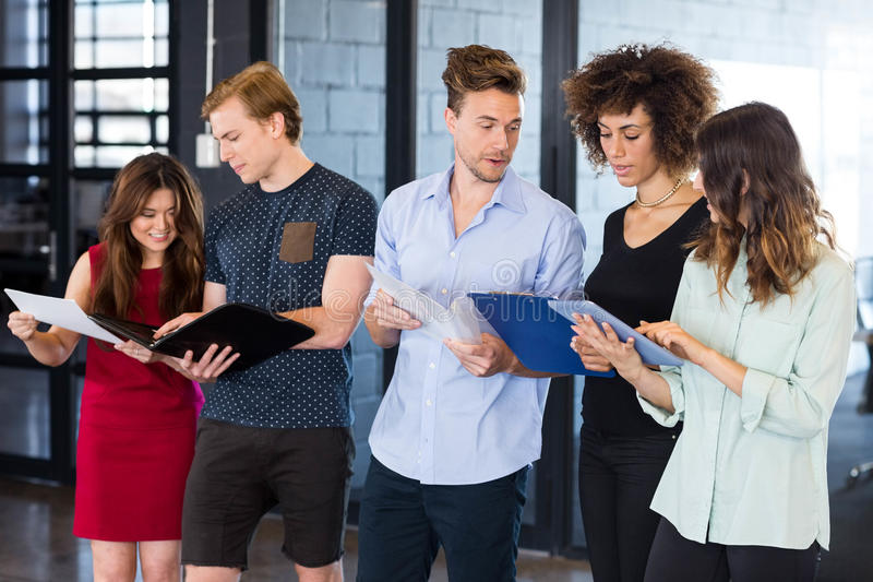 Colleagues standing with document and digital tablet royalty free stock photo