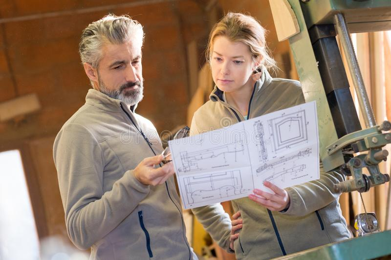 Colleagues stood by band saw looking at design drawings. Bench stock photo