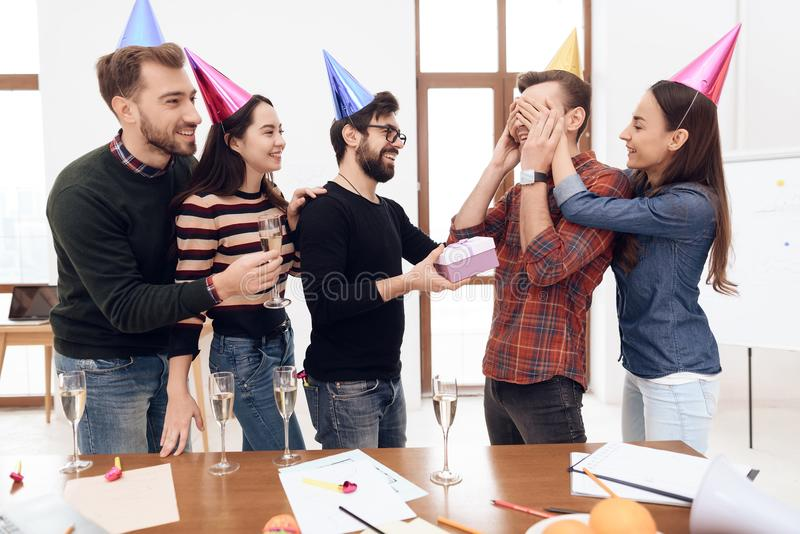 Colleagues surprise another employee of the company. They have caps on their heads. They are in a good mood stock photo
