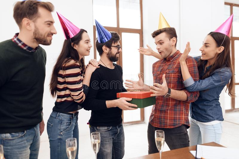 Colleagues surprise another employee of the company. They have caps on their heads. They are in a good mood royalty free stock photos