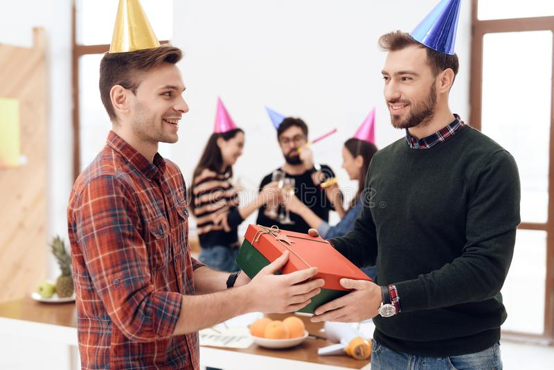 Colleagues surprise another employee of the company. They have caps on their heads. They are in a good mood stock images