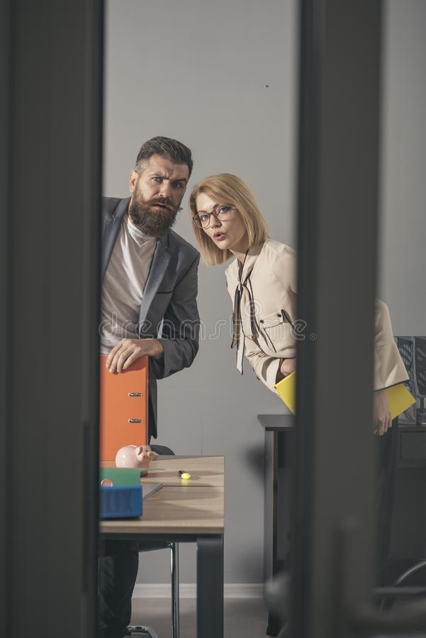 Colleagues with troubled faces look out modern office. Colleagues at meeting in office with glass walls royalty free stock images