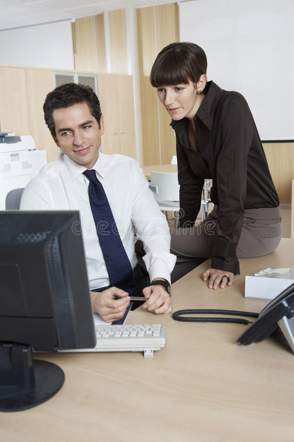 Download Colleagues Using Computer At Desk In Office Stock Photo - Image: 33825832
