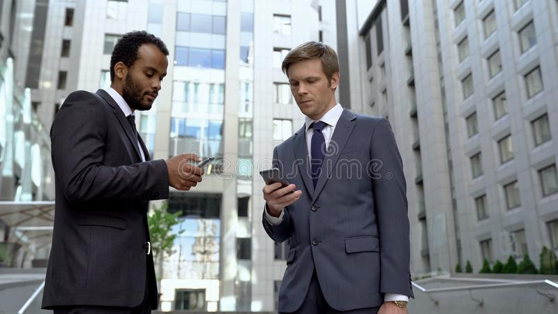 Colleagues using smartphones for online banking app convenient money transaction royalty free stock photo