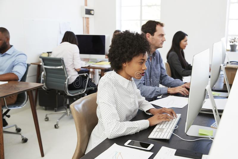 Colleagues work at computers in open plan office, side view stock photo