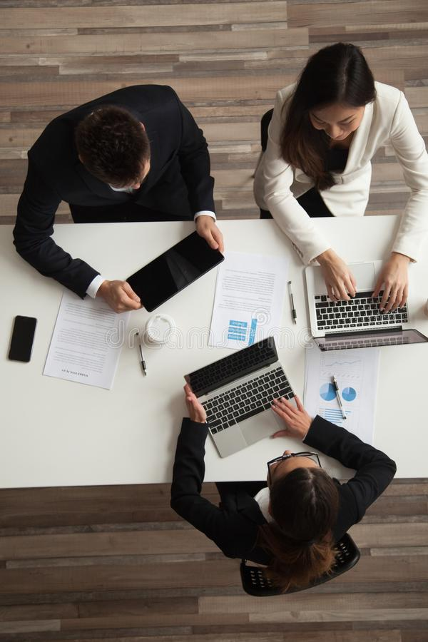Free Colleagues Working Together At Meeting Using Devices, Top Vertic Royalty Free Stock Photos - 117906578