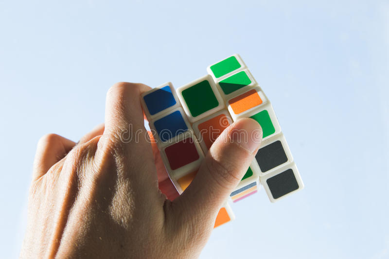 Collect parts of fate. A colorful cube of a rubik in the hands of a man royalty free stock photo
