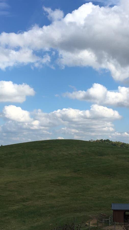 Collecte des nuages au-dessus de pré verdoyant photo libre de droits