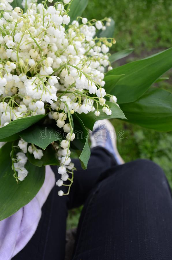 Bouquet of lilies in the hand of the girl. royalty free stock photography
