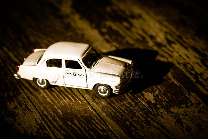 Collectible toy model of an old car with a taxi symbol on a wooden background. Selective focus. Copy space.  stock photo