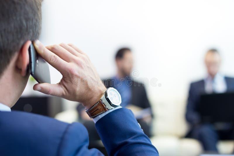 Collectief commercieel team bij commerciële vergadering en manager die op telefoon spreken royalty-vrije stock afbeeldingen