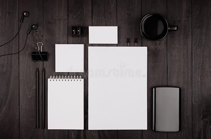 Collectief identiteitsmalplaatje, lege die kantoorbehoeften met koffie wordt geplaatst en oortelefoon op zwarte modieuze houten a royalty-vrije stock foto's