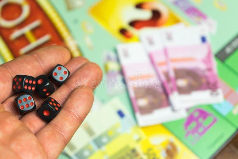 Collectief Raadsspel De mens werpt spelkubussen op het speelgebied royalty-vrije stock fotografie