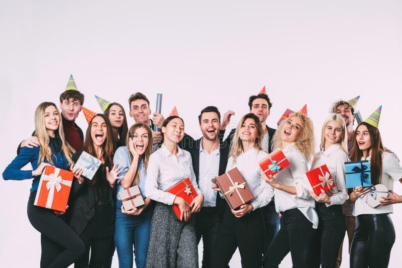 Collectief, viering en vakantieconcept - gelukkig team met giften die de partij van de pretverjaardag hebben royalty-vrije stock foto