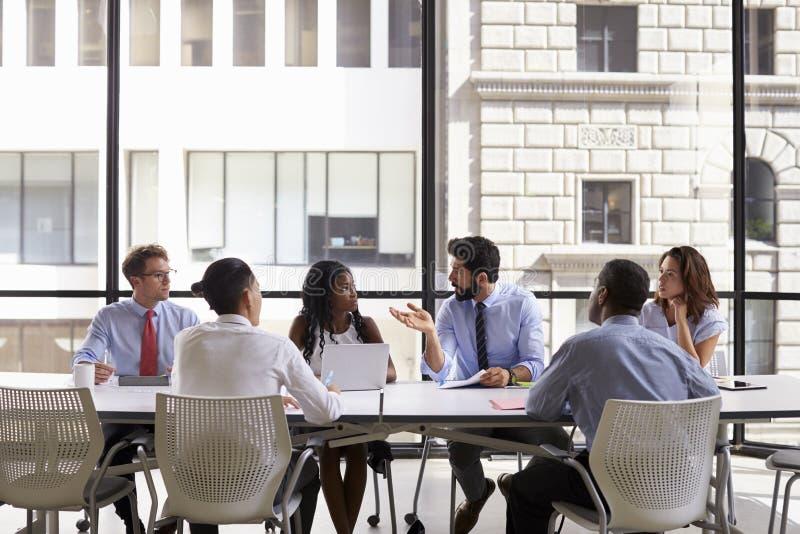 Collectieve commerciële teamvergadering in een modern open planbureau stock afbeeldingen
