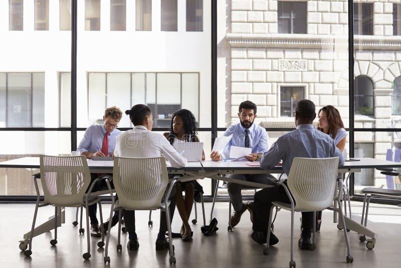 Collectieve commerciële teamvergadering in een modern open planbureau stock afbeelding
