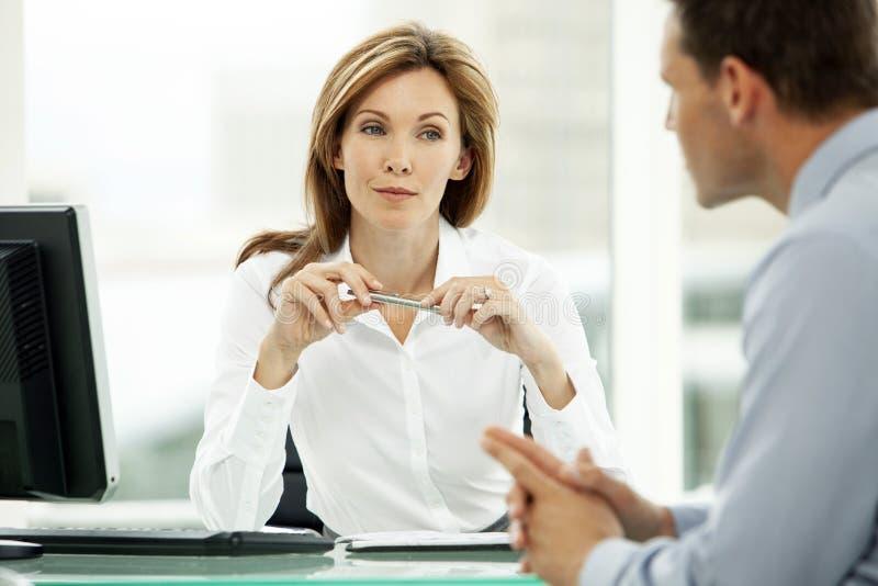 Collectieve directeurvrouw die aan jonge zakenman in bureau luisteren royalty-vrije stock foto