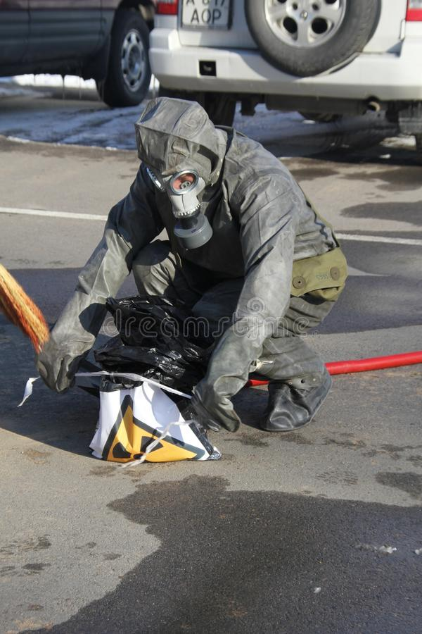 Collecting hazardous material. Man in radiation protection suit collecting hazardous material in black garbage bag stock photo