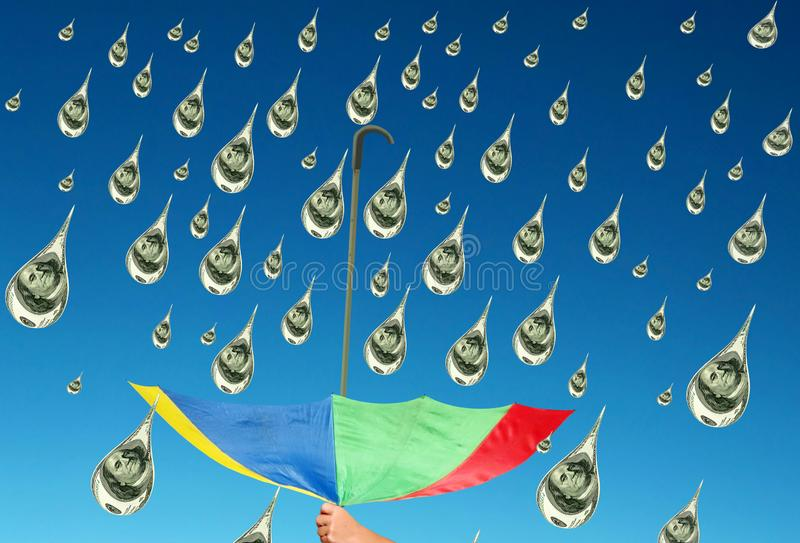 Collecting money rain. Blue sky. Concept of success. The hand of man is holding the upturned colorful umbrella to collect USD as water drops of rain on the royalty free stock image