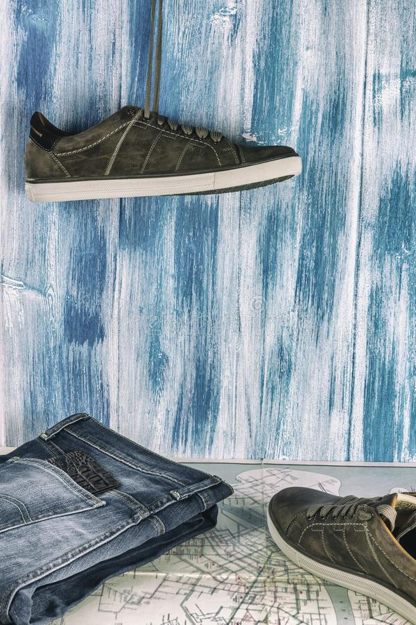 Collecting to travel. Jeans, passport, sneakers and a map on a wooden background. Summer travel. stock image