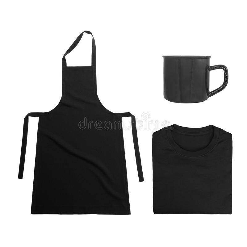 Collection of black objects isolated on white background. Black blank apron, black folded t-shirt, metal mug. Flat lay stock photo
