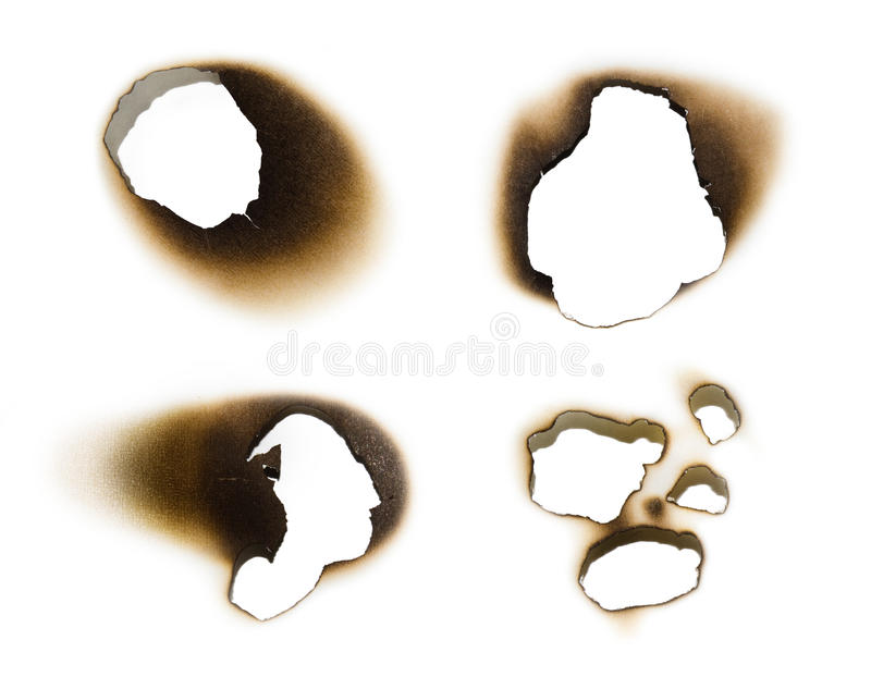 Collection of burnt holes in a piece of paper stock photo