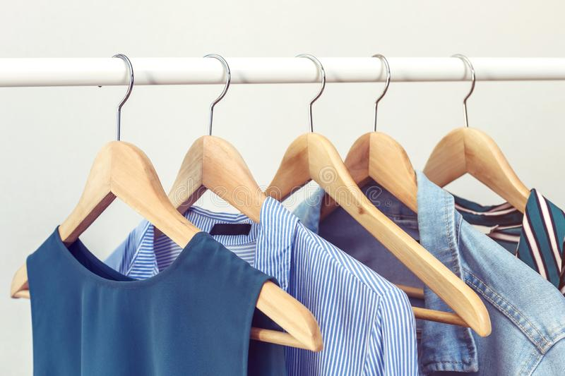 Collection of clothes hanging on rack near white wall. royalty free stock photography